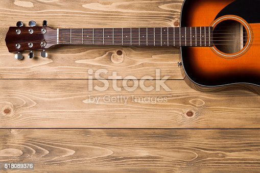 istock Acoustic guitar on wooden background 518089376