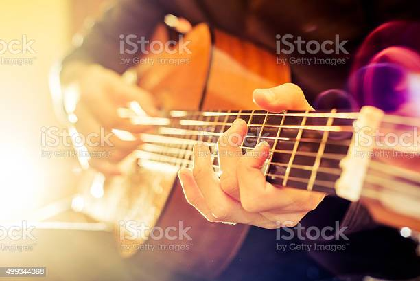 the young guy playing an acoustic guitar. Shooting backlit