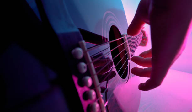 Acoustic guitar played by a girl and colorful lights stock photo