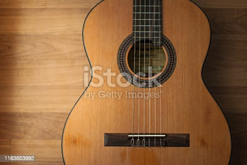 istock Acoustic guitar resting against a wooden background 1163653992