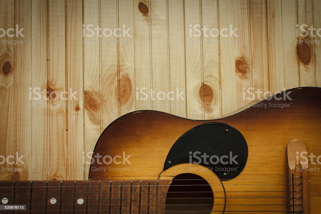 Acoustic guitar resting against a wooden background stock photo