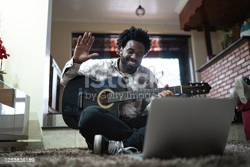 Acoustic guitar teaching through a video call, waving to laptop