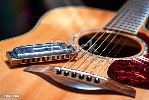 Acoustic guitar with country blues harmonica ready on stage