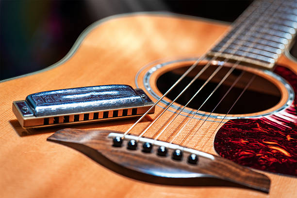 Acoustic guitar with blues harmonica country Acoustic guitar with country blues harmonica ready on stage folk music stock pictures, royalty-free photos & images