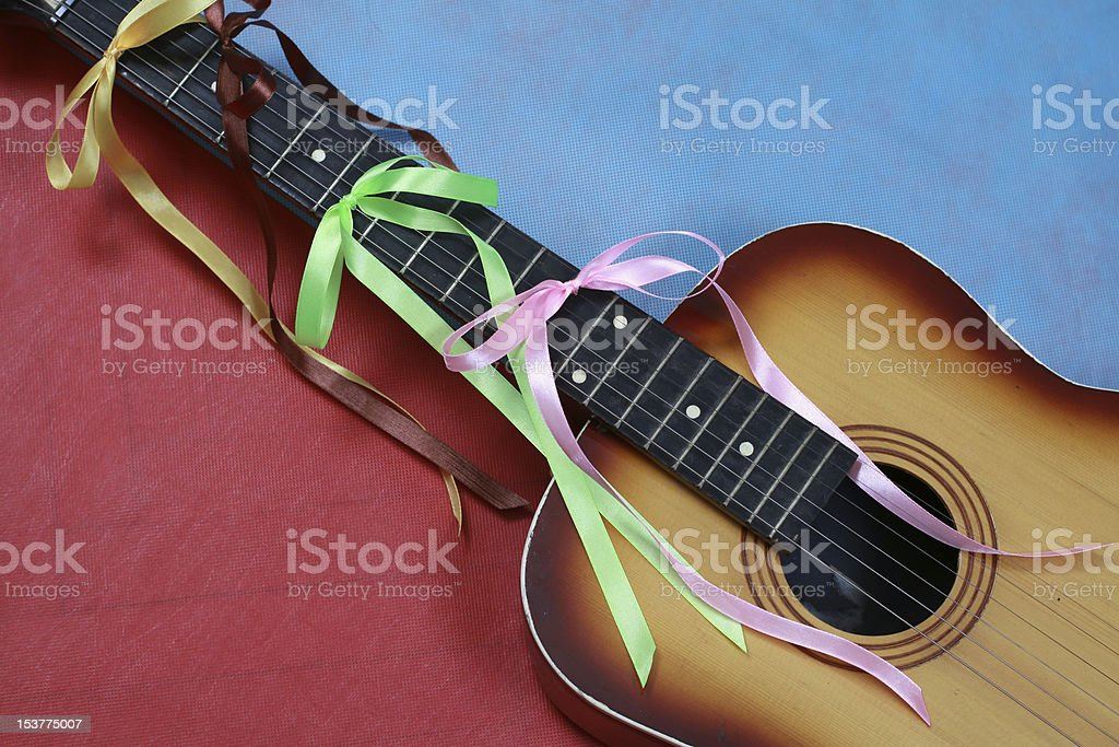 Acoustic Guitar With Ribbons Tied In Bows Isolated On Blue/Red royalty-free stock photo