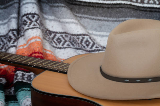 Acoustic guitar with Santa Fe style hat with a Mexican style blanket in the background stock photo