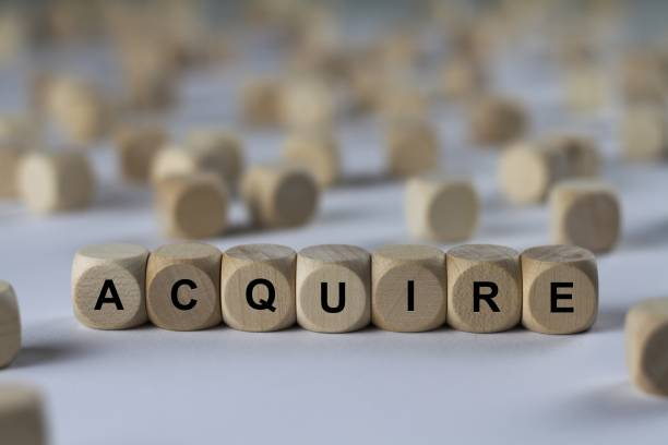 acquire - cube with letters, sign with wooden cubes stock photo