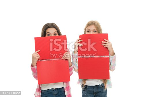 istock Acquiring knowledge from the texts they are reading. Playful small girls covering faces with books at reading lesson. Little children learn reading and writing at school. Reading comprehension skills 1176960655