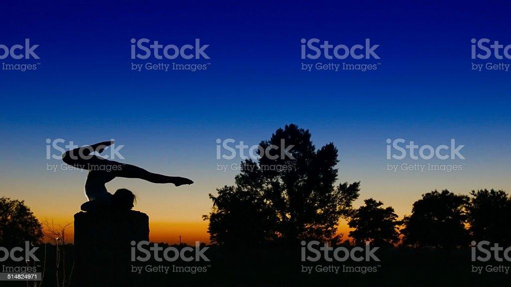 Acrobat girl exercising on column in the evening  Arrow position stock photo