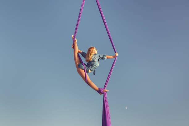 acrobat in den himmel auf der leinwand. - trapez stock-fotos und bilder