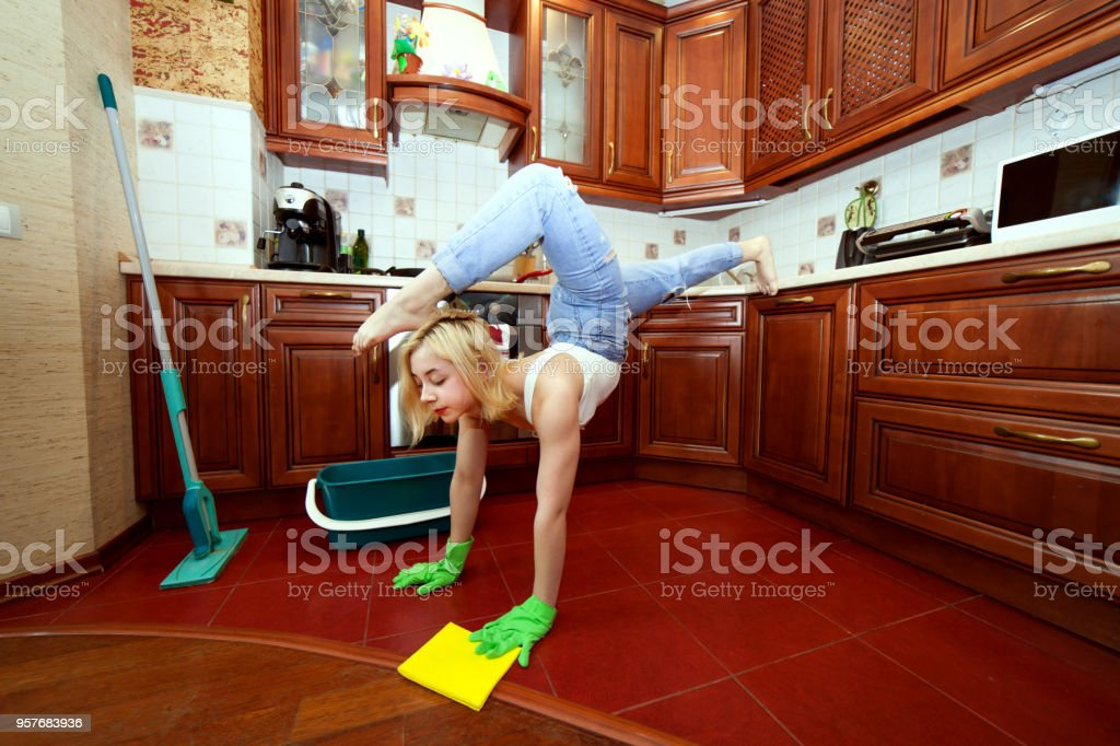 Acrobat woman is cleaning an apartment. stock photo