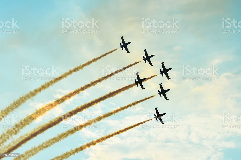 Acrobatic planes doing acrobatics at an Airshow flying at sunset stock photo