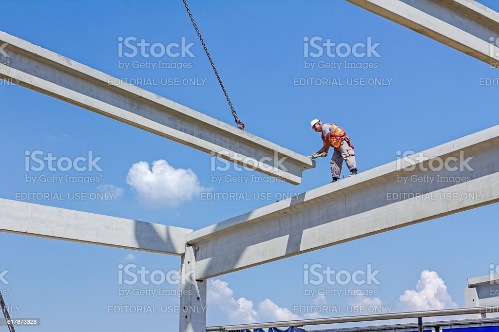 Acrobatic way of assembly concrete joist. Placing the truss. stock photo