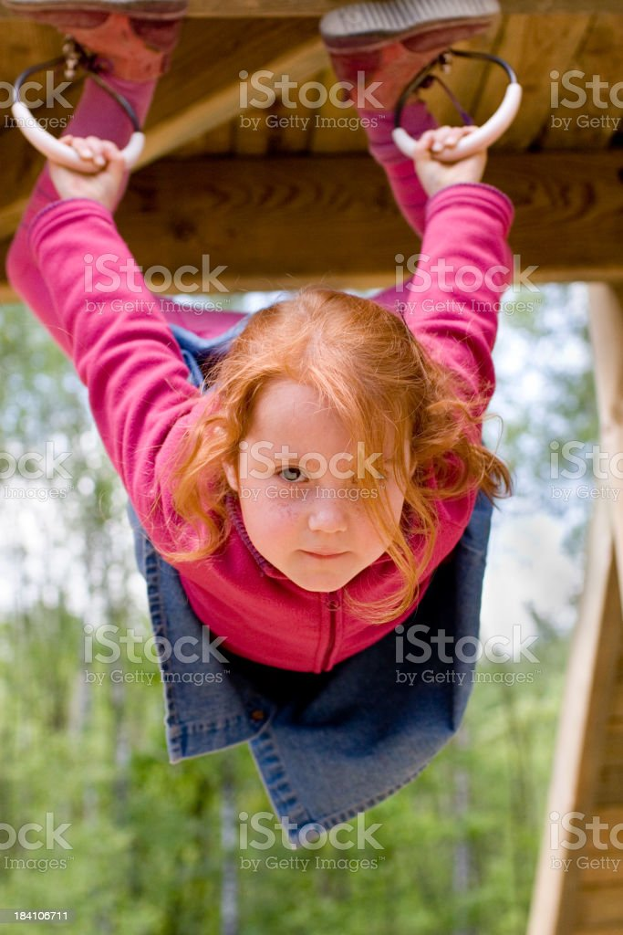 Acrobatic young girl at the playground Happy little girl at the playground. Holding real tight. Serious look. Activity Stock Photo