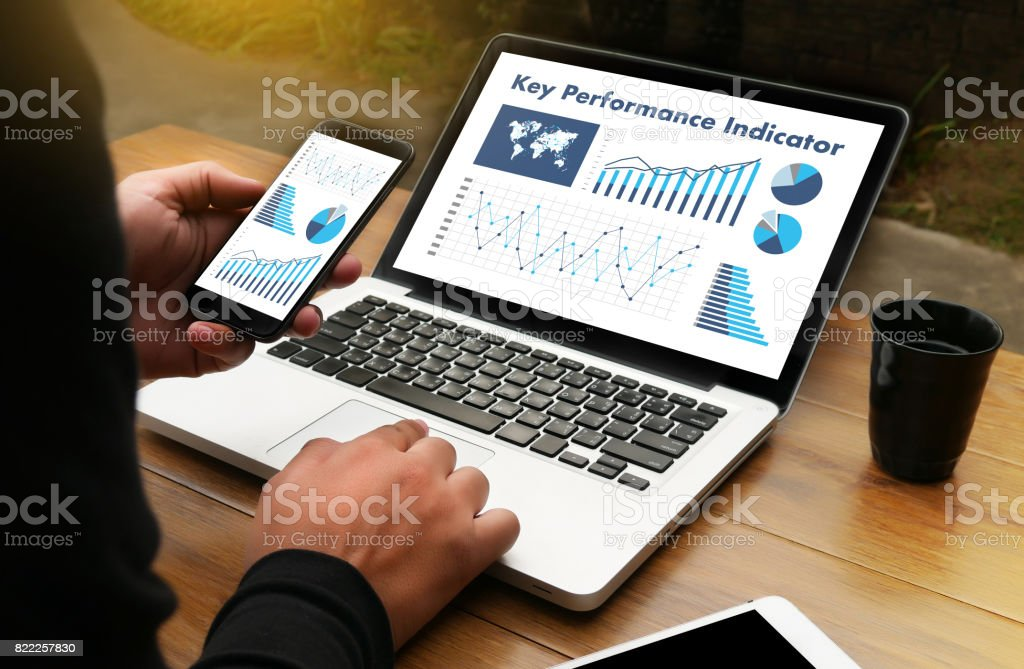 KPI acronym (Key Performance Indicator) Business team hands at work with financial reports and a laptop stock photo