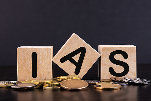 IAS - acronym from wooden blocks with letters, abbreviation IAS International Accounting Standards concept, coins background