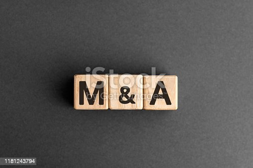 M&A - acronym from wooden blocks with letters, mergers and acquisitions M&A concept,  top view on grey background