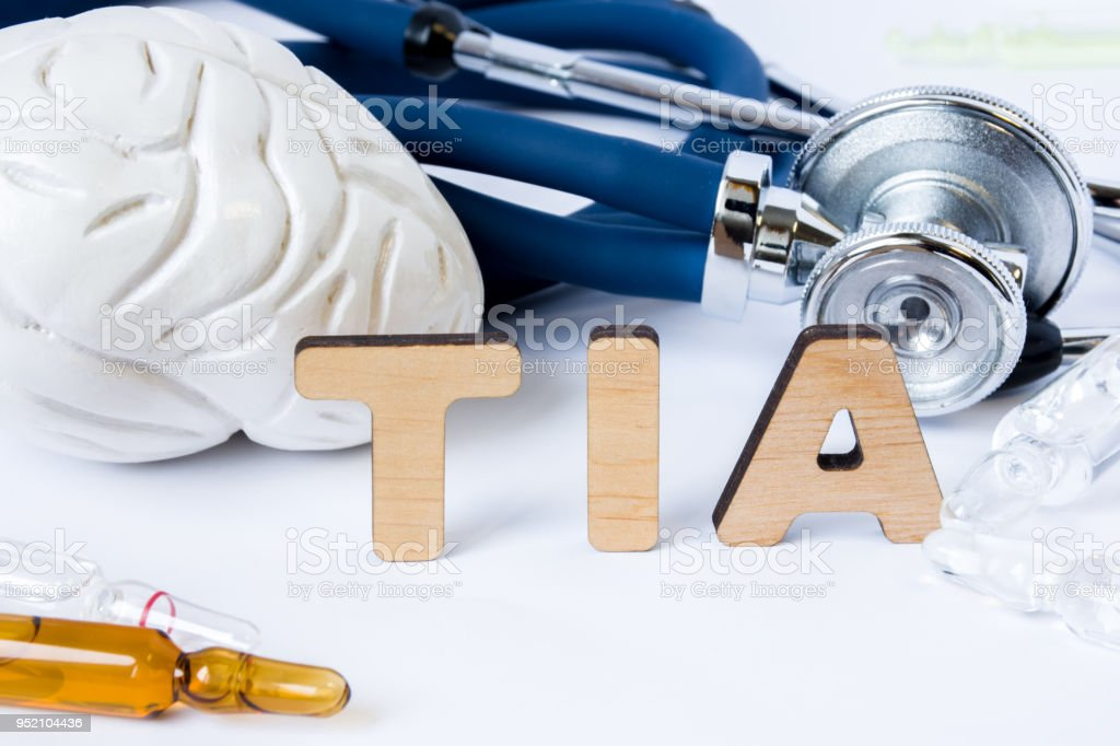 TIA Acronym or abbreviation to medical concept or diagnosis of transient ischemic attack or small brain stroke. Word TIA stands among models of the brain, stethoscope and medicines in ampules or vials stock photo