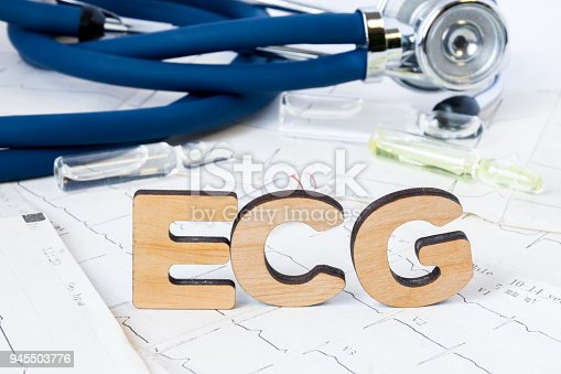 istock ECG Acronym or abbreviation to medical dignostics of electrocardiogram - cardiac test that measures electrical impulses in heart. Word ECG letters stands on printed strips of examples of EKG 945503776