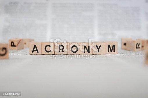 istock Acronym Word Written In Wooden Cube - Newspaper 1143496243