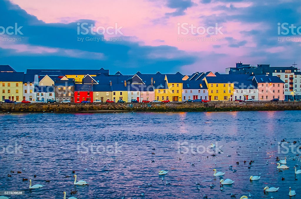Across Galway Harbour, Ireland Shot from the Claddagh area looking straight across Galway Harbor into Old Galway Town with it's Pastel building and swans. Bay of Water Stock Photo