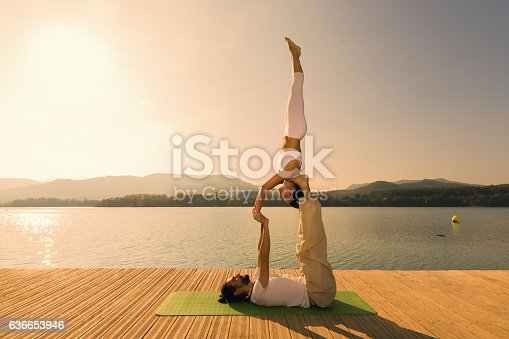 Couple practicing acroyoga in nature at beautiful lake at sunset Acroyoga star pose