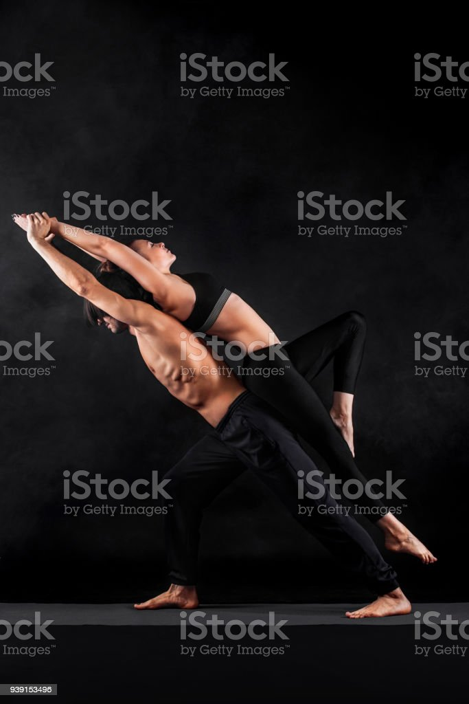 Acroyoga. Young couple practicing acro yoga on mat in studio together. Couple yoga. Partner yoga. Black and white photo. stock photo