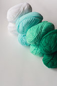 acrylic soft pastel green, azure and white colored wool yarn thread skeins row on white background, top angle view, vertical stock photo image with copy space for text