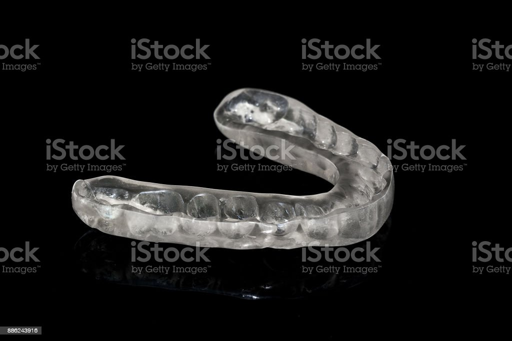 Acrylic transparent dental Mouth Guard on black background, showing reflection stock photo