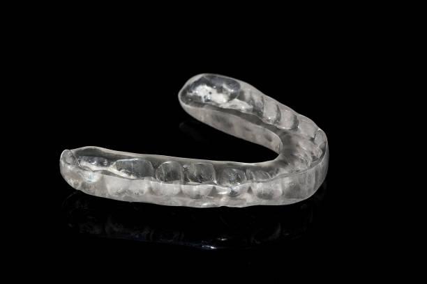 acrylic transparent dental mouth guard on black background, showing reflection - fare la guardia foto e immagini stock
