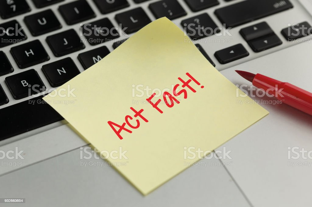 Act Fast! sticky note pasted on the keyboard stock photo