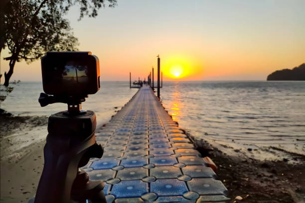 Action camera mounted on a tripod photograph the pier and sunrise on the beach stock photo