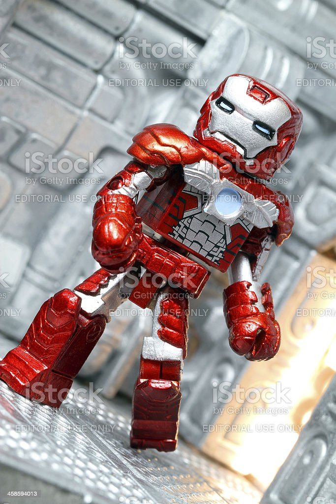 A toy Iron Man posed on a futuristic background. The Iron Man...
