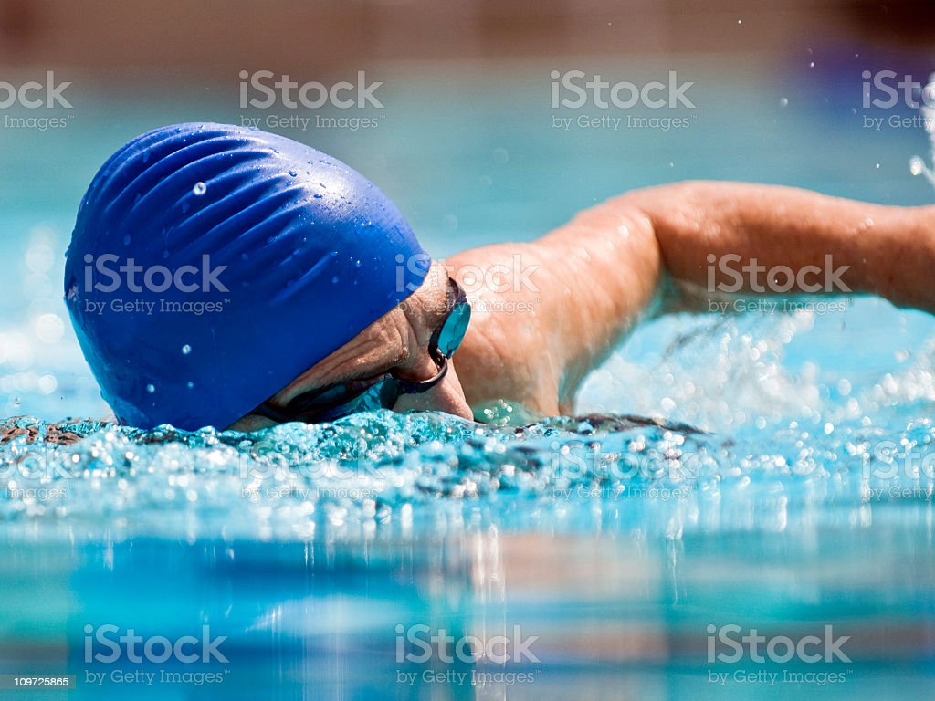 Action Image of a senior female swimmer stock photo