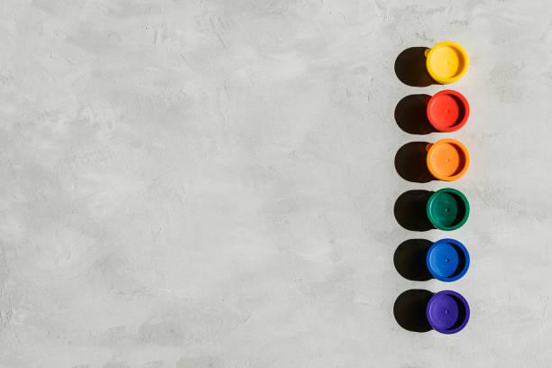 aksiyon boyama, trend sanat arka plan. yuvarlak kavanozlarda çok renkli boyalar ve kopya alanı ile gri bir beton arka plan üzerinde fırça. sert ışık. - tempera resim stok fotoğraflar ve resimler