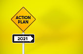 istock Action Plan 2021 Directional Road Sign On Yellow Background 1256297563