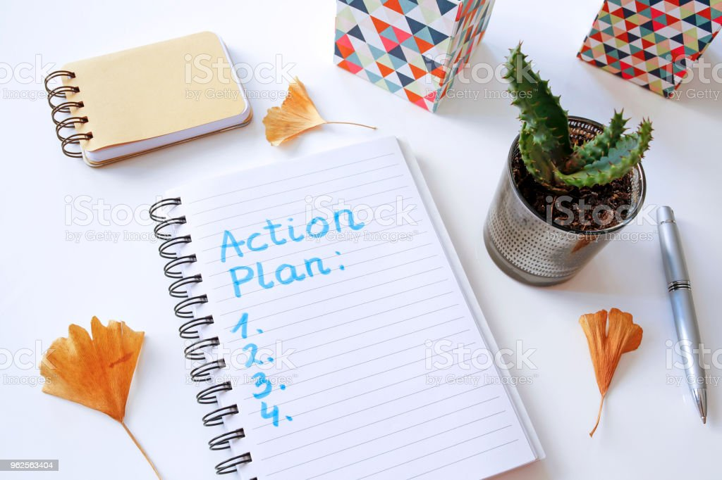 action plan written in notebook stock photo