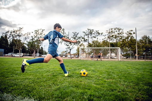 Low angle rear view of 12 year old male athlete wearing blue uniform and approaching ball to kick toward goal.