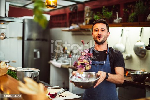 Young man preparing fresh food in commercial kitchen, looking at camera, fresh ingredients mid air