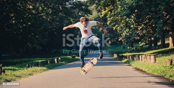 Action shot of a skateboarder skating, doing tricks and jumping on the road through the forest. Free riding skateboard