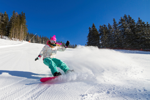 Action shot of a snowboarding girl, zooming downhill