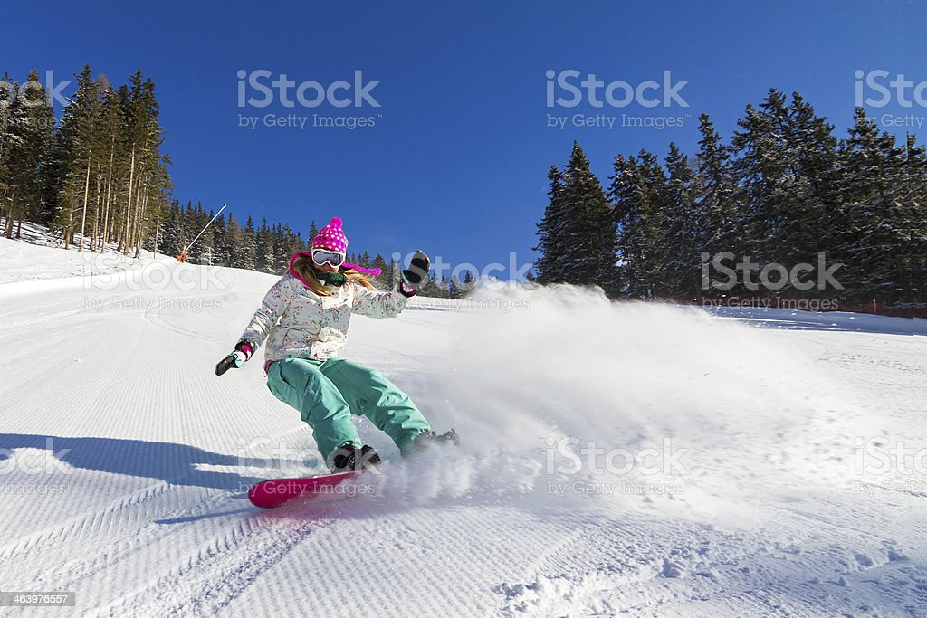 Action shot of a snowboarding girl, zooming downhill stock photo