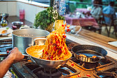 Cooking handmade spaghetti and tomato in busy kitchen of small restaurant, ingredients, mid air, skill, heat