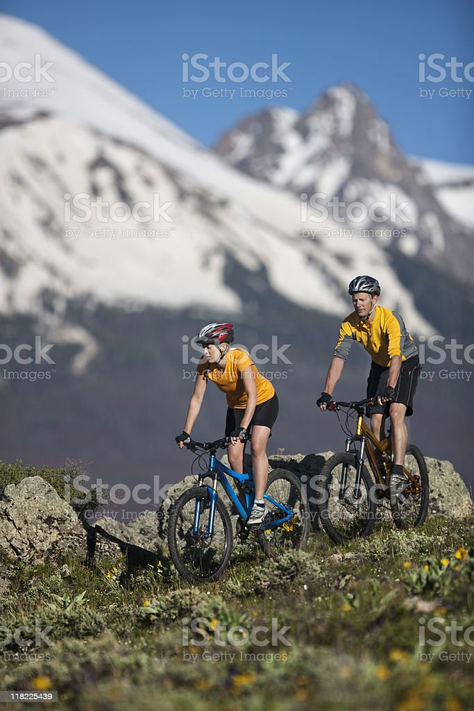 Action Shot Of Couple Mountain Biking In Colorado Rockies royalty-free stock photo