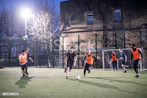 istock Action shot of footballers on an urban pitch at night with two players running for the ball 963295628