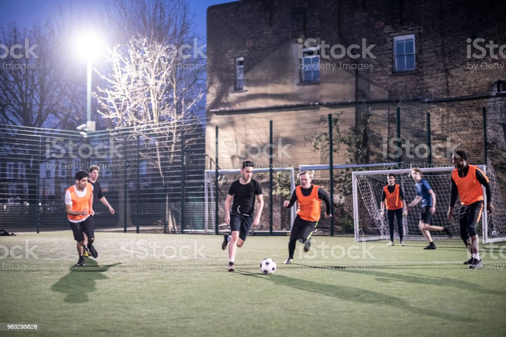 Action shot of footballers on an urban pitch at night with two players running for the ball stock photo