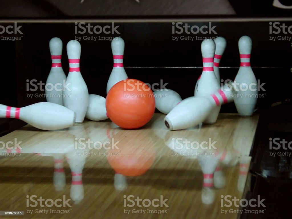 Orange bowling ball hitting ten pins two are falling.