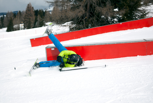 Action shot of skier falling off rail in a Snowpark