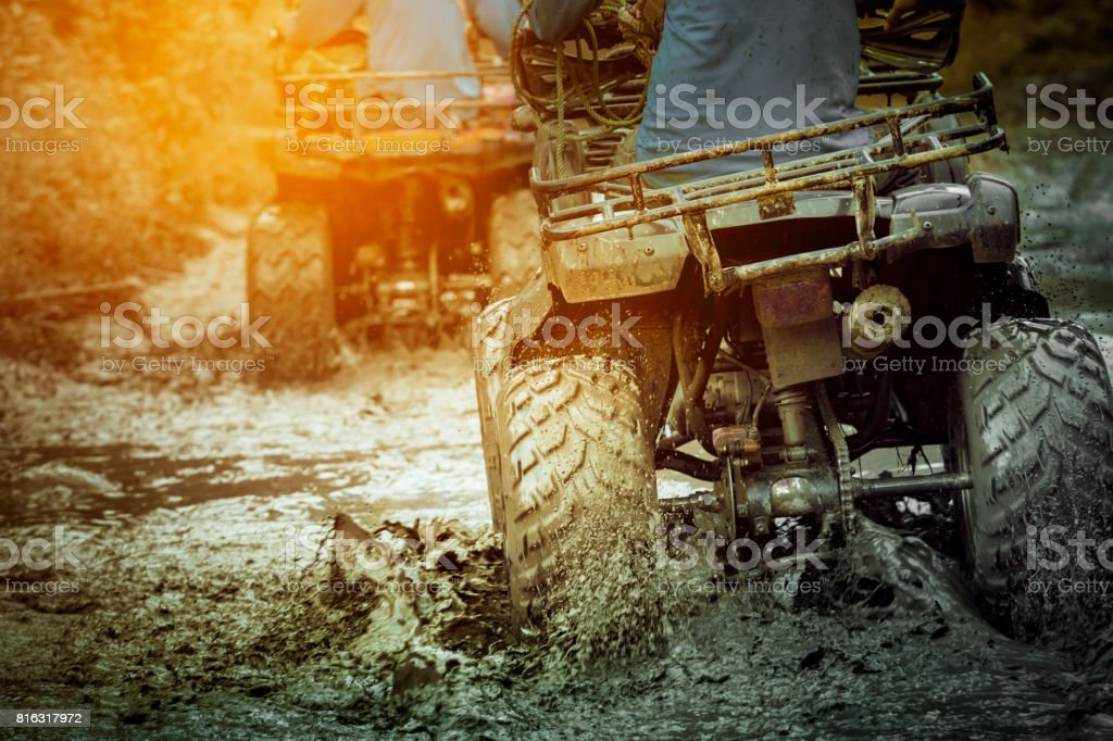 action shot of sport atv vehicle running in mud track stock photo