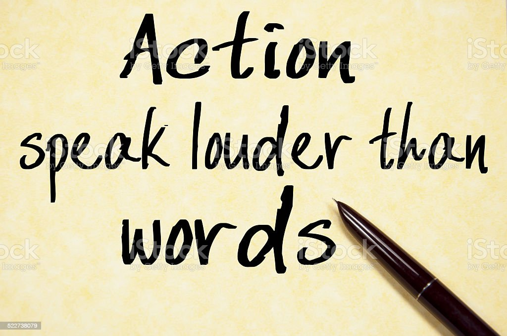 action speak louder than words text write on paper stock photo